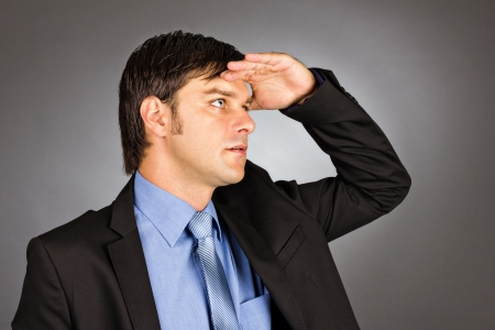 Young businessman holding his hand at forehead and looking forward against gray background Stock Photo - 24108011