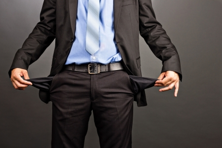 Business man showing his empty pockets isolated on gray