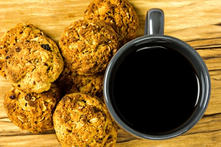 Cookies and cup of coffe isolated on wood photo