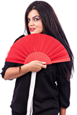 Portrait of a brunette young woman holding red fan against white background photo