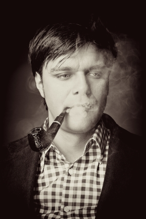 Retro portrait of a gentleman smoking pipe on black background photo