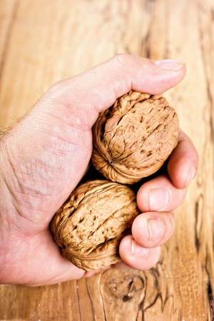 Hand holding walnuts.Wooden background photo