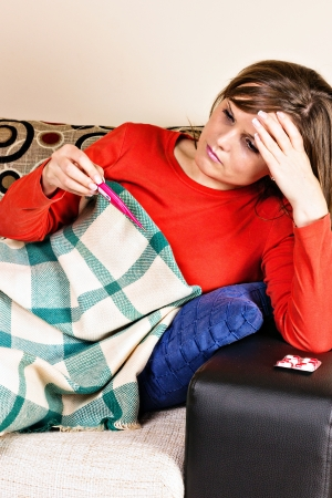 Young woman having flu and taking her temperature at home photo