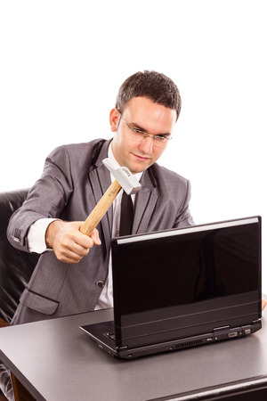 Young businessman with a hammer ready to smash his laptop while sitting at office desk isolated on white  photo
