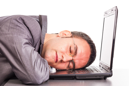 hardworker: Closeup of  a overworked young businessman taking a nap on his laptop on white background