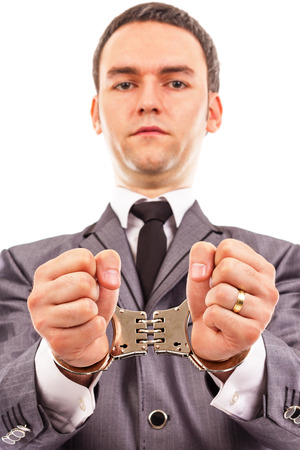 handcuffed hands: Closeup portrait of a young businessman with handcuffed hands. White background
