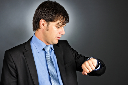 Young businessman looking at his watch against gray background photo