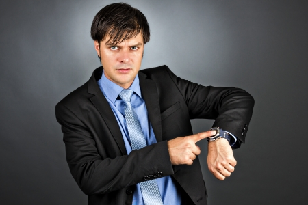 impatience: Young businessman pointing to his watch with an angry expression on his face isolated on gray background