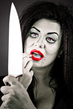 Portrait of a brunette young woman applying lipstick using the knife as a mirror against gray photo
