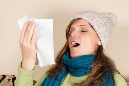 Young woman sneezing in a tissue in the living room, having flu photo