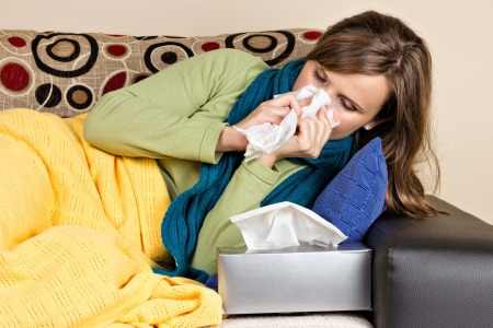 Young woman at home having flu, blowing her nose  photo