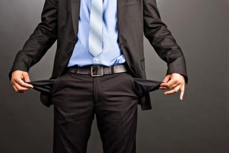 Bedrijfs mens die zijn lege zakken op een grijze achtergrond