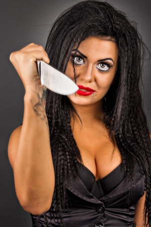 Portrait of an expressive young woman with creative make-up holding a big knife isolated on gray background photo
