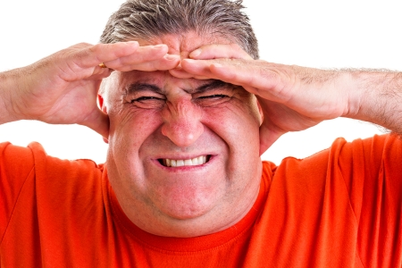 Portrait of an expressive man suffering from a severe headache against white background