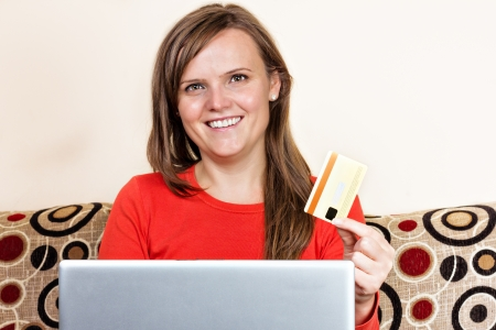 Young woman smiling and  using her credit card for online shopping at home photo