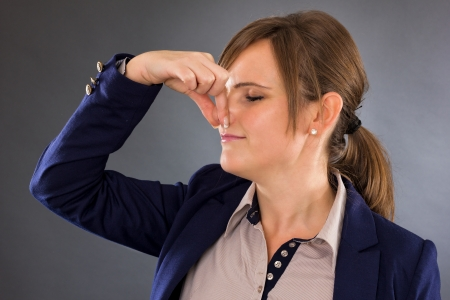 stink: Closeup portrait of a young businesswoman holding her nose because of a bad smell on gray Stock Photo