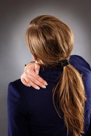 crick: Closeup ritratto di una giovane imprenditrice che soffrono di dolore al collo isolato su sfondo grigio