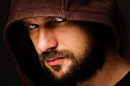 Close-up portrait of threatening  man with beard wearing a hood against gray background