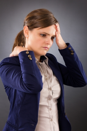 Portrait of a young businesswoman suffering from neck pain isolated on gray background photo