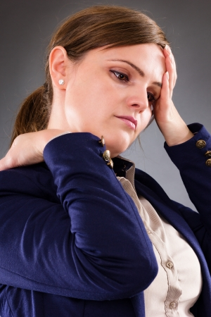 Closeup portrait of a young businesswoman suffering from neck pain over gray  backgorund