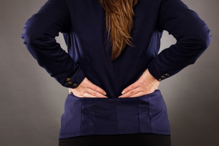 Closeup of businesswoman with back pain on gray background photo