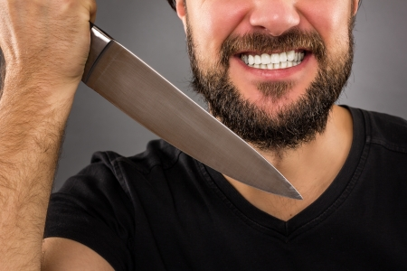 Closeup portrait of a threatening man with beard holding a knife in his hands over gray background  photo