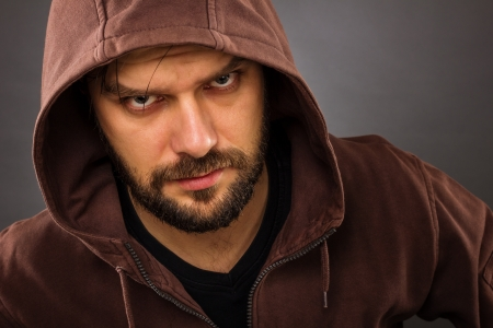 threatening: Close-up portrait of threatening man with beard wearing a hood against gray background