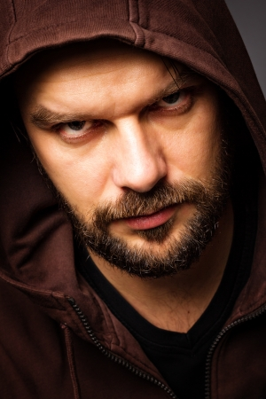 Close-up portrait of threatening  man with beard wearing a hood against gray background photo