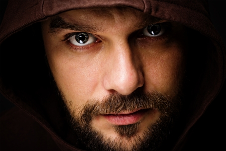 Close-up portrait of threatening man with beard wearing a hood  Stock Photo