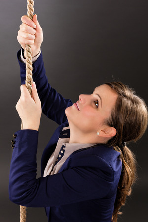 Closeup portrait of a young businesswoman trying to climb a rope-carreer concept- isolated on gray background photo