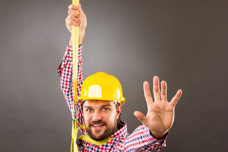 Young construction man with hard hat wearing  a fall protection harness and lanyard for work at heights saluting.Gray background photo