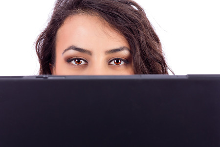 Young businesswoman holding a laptop in front of her face, can only see her eyes, isolated on white background  photo