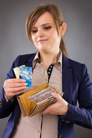 Portrait of a smiling businesswoman holding her wallet and credit cards in hands isolated gray background photo
