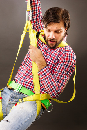Young man wearing  a fall protection harness and lanyard for work at heights looking down. Gray background photo
