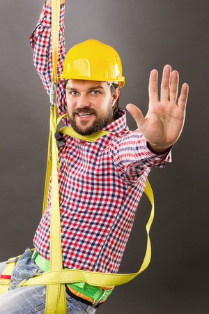 Young construction man with hard hat wearing  a fall protection harness and lanyard for work at heights saluting.Gray background Standard-Bild
