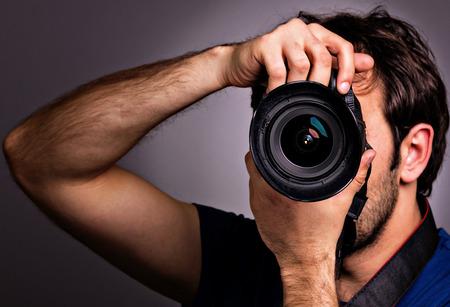 전문 카메라와 함께 젊은 남자가 회색 배경에 고립입니다. 스톡 콘텐츠