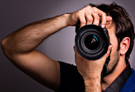 Jeune homme avec appareil photo professionnel isolé sur fond gris. Banque d'images - 25976079