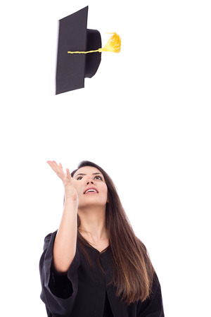 alumna: Beautiful female student throws up his graduation cap in celebration.White background