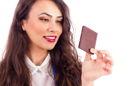 tempted: Beautiful woman tempted by chocolate isolated on white background