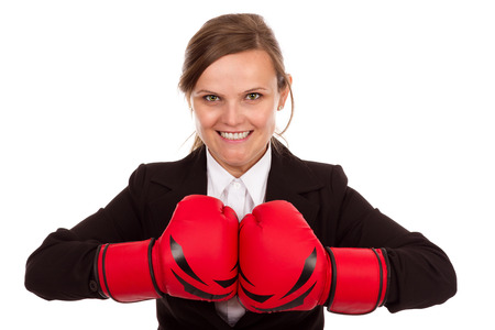 Attractive businesswoman punching red boxing gloves together ready to fight  isolated on white background. Stock Photo