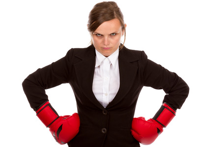 Young businesswoman standing with hands on hips wearing boxing gloves ready for the competition isolated over white background photo