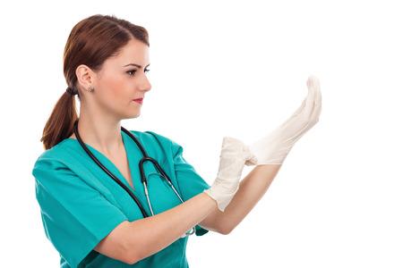 Femme médecin attrayant putting stérilisé gants chirurgicaux isolé sur fond blanc