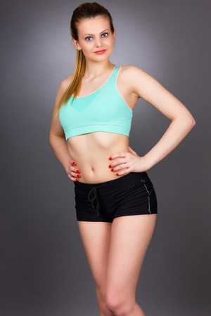 Portrait of a beautiful sports woman with hands on hips on gray background photo