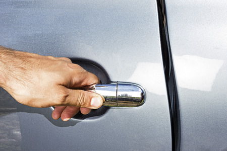 Closeup of  man hand opening a car door photo