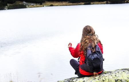 stillness: Young woman admiring the stillness of mountain  lake.Back view