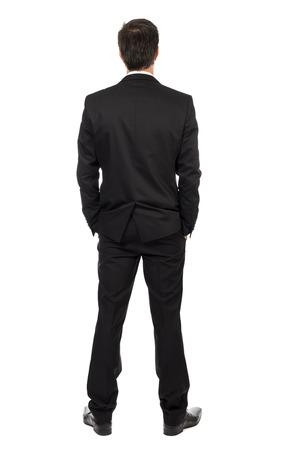 detras de: Retrato de cuerpo completo del joven empresario, la vista atrás, con las manos en el bolsillo aisladas sobre fondo blanco