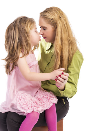 cute little girls: Mother kissing and playing with her lovely daughter over white  background