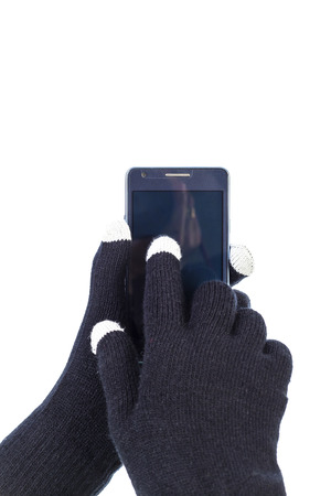 Closeup of woman hands with touchscreen gloves holding smart phone.White background photo