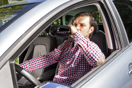drinking driving: Young businesssman drinking alcohol while driving his car Stock Photo