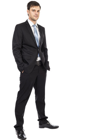 only adult: Full body portrait of  young business man holding hands in his pockets  isolated over white background